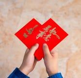 Kid holding red pockets shaped like a heart Stock Photos