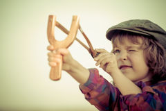 Kid holding slingshot. In hands against summer sky background. Retro style royalty free stock photos