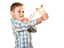 Kid holding slingshot in hands. Children upbringing problems. Kid holding slingshot in hands. Bad naughty boy shoots from a wooden sling on white royalty free stock images