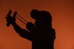 Kid holding slingshot in hands Stock Image