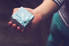 Kid holding a small blue gift box with ribbon in his hand. Top view close up of child holding a blue gift box with ribbon in his hand royalty free stock photography