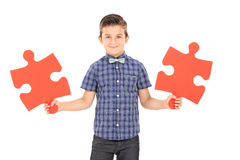 Kid holding two pieces of a puzzle Royalty Free Stock Photos
