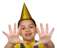 Kid holding up ten fingers. Four year old Hispanic preschooler boy wearing a gold birthday party hat holding up ten fingers, isolated on white background Royalty Free Stock Photos