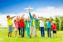 Kid holding white airplane toy and children behind. View of kid holding big white airplane toy and children standing behind in the field during summer day Royalty Free Stock Photos