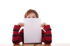 Kid holding a white sheet of paper in his hand Stock Images