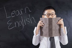 Kid holds book with text Learn English Royalty Free Stock Photos