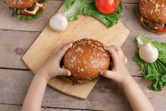 Child holds mushroom burger, raw vegetables around stock photography