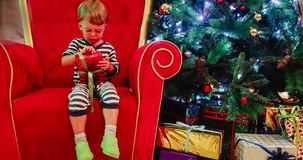 Adorable little baby boy having fun on a christmas eve. Kid holds his gift and rejoices. Adorable little baby boy having fun on a christmas eve, smiling stock footage