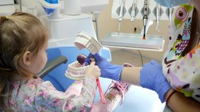Kid holds toothbrush and cleans teeth of an artificial jaw in dentist hands in office with modern equipment. Kid holds toothbrush and cleans teeth of an stock footage