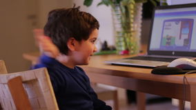 Kid at home wave his hand and turn to his computer screen stock video footage