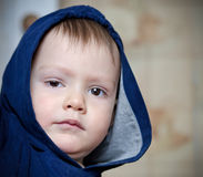 Kid in a hood. Little boy in a jacket with a hood close up Royalty Free Stock Image