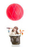 Kid on hot air balloon watching through spyglass Stock Photos