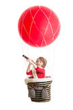 Kid on hot air balloon watching through spyglass Royalty Free Stock Images