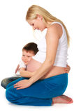 Kid hugging his pregnant mother Stock Photography