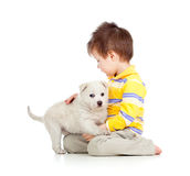 Kid hugging puppy on white background Stock Images