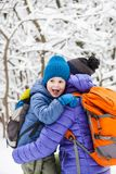 The kid hugs Mom. A boy and his mother are walking in the winter forest. A child kisses his mother. The women supports her son. Motherhood royalty free stock photo