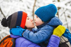 Mom hugs the child. The kid hugs Mom. A boy with his mother on a winter walk. A child kisses his mother. The women supports her son. Motherhood. The family royalty free stock images
