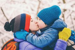 Mom hugs the child. The kid hugs Mom. A boy with his mother on a winter walk. A child kisses his mother. The women supports her son. Motherhood. The family royalty free stock photos