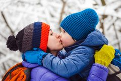 The kid hugs Mom. A boy and his mother are walking in the winter forest. A child kisses his mother. The women supports her son. Motherhood royalty free stock images