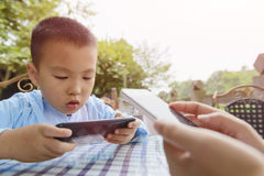 Kid indulge in smartphone. Chinese kid indulge in smartphone game, and parent doing same thing outdoor royalty free stock photography
