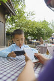 Kid indulge in smartphone. Chinese kid indulge in smartphone game, and parent doing same thing outdoor royalty free stock images