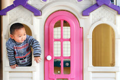 A kid inside a doll house Royalty Free Stock Images