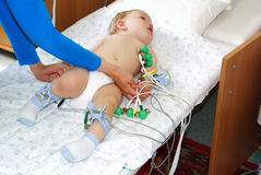The kid on inspection in hospital. The little child with tear-stained eyes lays on a couch in hospital and to it do the heart cardiogramme Royalty Free Stock Photos