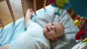 The kid joyfully reacts to the new toy. Mobile in the crib for the baby. The child follows the eyes of the toy, moves