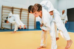 Kid judo, young fighters on training, self-defense. Little boys in kimono practice martial art stock image