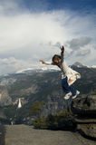 Kid Jumping. Little girl jumping from a rock with mountains in the background Stock Images