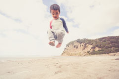 Kid jumping on beach. Royalty Free Stock Images