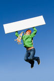 Kid jumping with blank board Royalty Free Stock Images