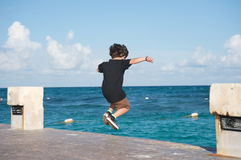 Kid jumping into the ocean Stock Image