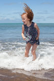 Kid jumping in the ocean waves. Happy little girl jumping in the ocean waves Royalty Free Stock Photography
