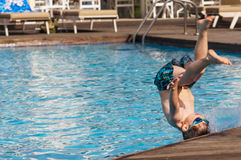 Kid jumping in the pool Stock Images
