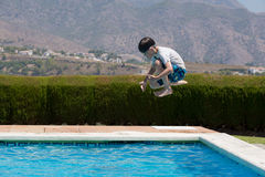 Kid jumping into pool Stock Photo