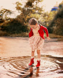 Kid jumping into a puddle Stock Photo