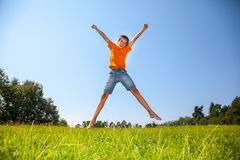 Kid jumping on the sunny meadow outdoors Royalty Free Stock Image