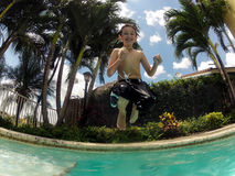 Kid jumping in swimming pool. Happy kid jumping into a swimming pool during summertime Stock Image