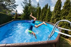 Kid jumping in swimming pool during staycation