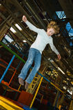 Kid jumping on trampoline. Child (8) jumping high on a trampoline in an indoor playground Royalty Free Stock Photos