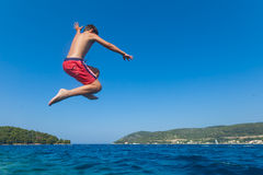Kid jumps in sea Royalty Free Stock Photo