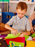 Kid keeps colored paper on table in kindergarten . Stock Image