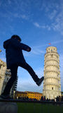 Kid kicking and fixing Pisa Tower Royalty Free Stock Images