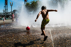 Kid kicking red ball in water fountain during the Summer Stock Photo