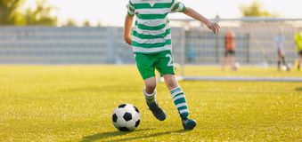 Kid kicking soccer ball. Close up action of boy soccer player running after ball. Aged 8-10, playing a football match stock photos