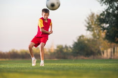 Kid kicking a soccer ball Stock Photos