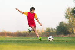 Kid kicking a soccer ball Royalty Free Stock Images