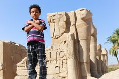 Kid with King statue ancient antiques at Karnak temple. Archaeology antiques and Egyptian statues at Karnak Temple located at Luxor city, Egypt. 20 September Royalty Free Stock Image