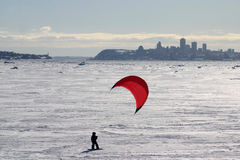 Kid kiting. On snow with city in background Royalty Free Stock Images